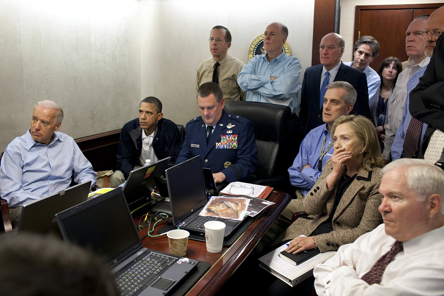 "May 1, 2011 ""Much has been made of this photograph that shows the President and Vice President and the national security team monitoring in real time the mission against Osama bin Laden. Some more background on the photograph: The White House Situation Room is actually comprised of several different conference rooms. The majority of the time, the President convenes meetings in the large conference room with assigned seats. But to monitor this mission, the group moved into the much smaller conference room. The President chose to sit next to Brigadier General Marshall B. ""Brad"" Webb, Assistant Commanding General of Joint Special Operations Command, who was point man for the communications taking place. WIth so few chairs, others just stood at the back of the room. I was jammed into a corner of the room with no room to move. During the mission itself, I made approximately 100 photographs, almost all from this cramped spot in the corner. There were several other meetings throughout the day, and we've put together a composite of several photographs (see next photo in this set) to give people a better sense of what the day was like. Seated in this picture from left to right: Vice President Biden, the President, Brig. Gen. Webb, Deputy National Security Advisor Denis McDonough, Secretary of State Hillary Rodham Clinton, and then Secretary of Defense Robert Gates. Standing, from left, are: Admiral Mike Mullen, then Chairman of the Joint Chiefs of Staff; National Security Advisor Tom Donilon; Chief of Staff Bill Daley; Tony Blinken, National Security Advisor to the Vice President; Audrey Tomason Director for Counterterrorism; John Brennan, Assistant to the President for Homeland Security and Counterterrorism; and Director of National Intelligence James Clapper. Please note: a classified document seen in front of Sec. Clinton has been obscured."" (Official White House Photo by Pete Souza)"