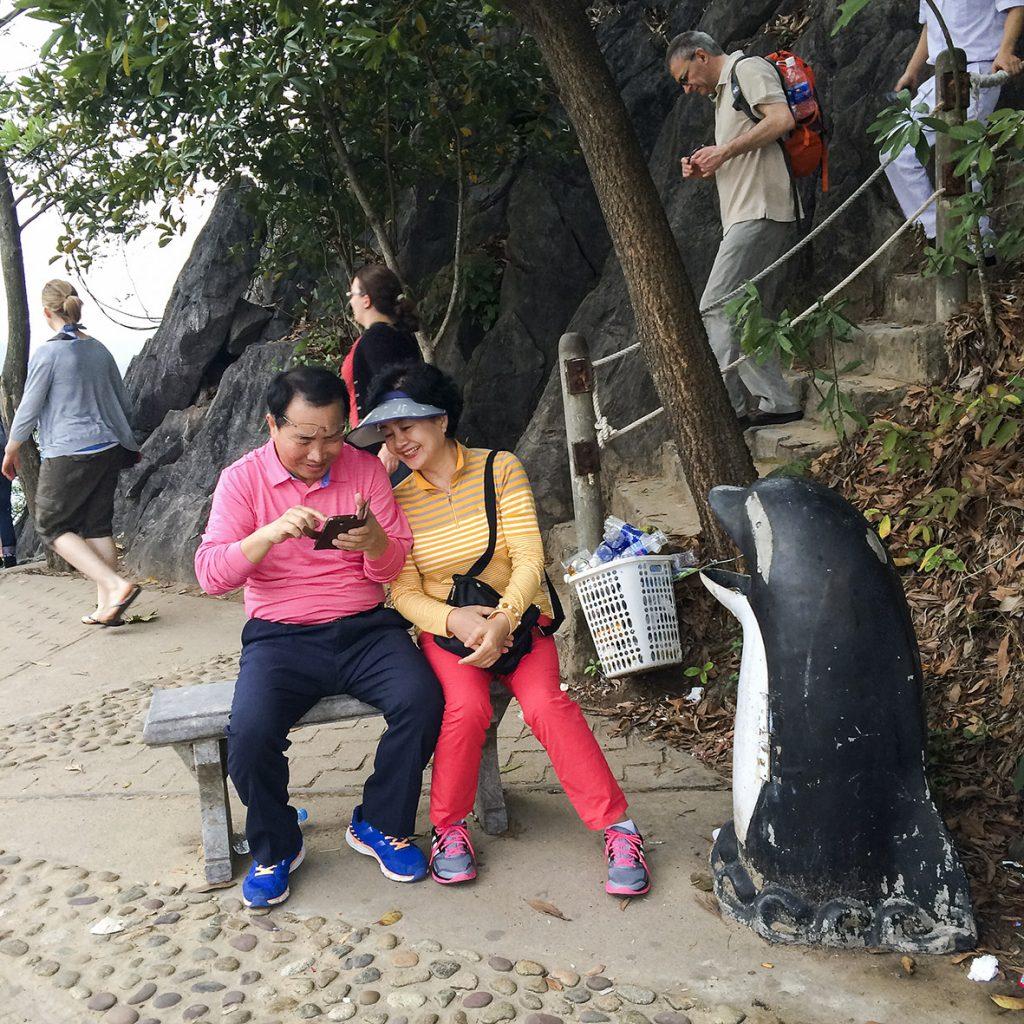 Zwei Touristen schauen auf Ti Top Island in Vietnam gemeinsam in ihr Smartphone, 21. Februar 2015. Foto: Mathias Schumacher