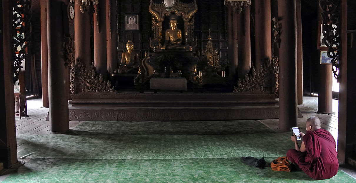 Ein Mönch sitzt in Inwa, in der Nähe von Mandalay, im hölzernen Bagaya-Kloster und schaut auf sein Smartphone. Foto: Mathias Schumacher